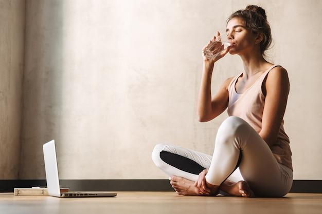 Фотография молодой красивой женщины в спортивной одежде, пьющей воду и сидящей на полу во время занятий йогой дома