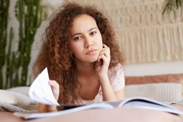 Фотография молодой отдохнувшей афроамериканской девушки с кудрявыми волосами, лежит на кровати и читает новый номер журнала, успокаивается, смотрит в камеру и трогает подбородок.