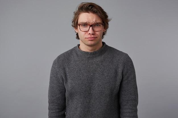 안경 젊은 슬픈 잘 생긴 남자의 사진은 회색 스웨터를 입고, 회색 배경 위에 서서 불행 해 보인다.