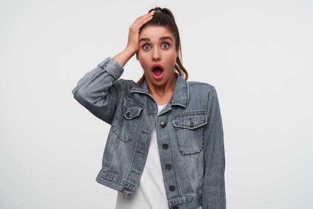 ショックを受けた若いブルネットの女性の写真は、白いtシャツとデニムのジャケットを着て、口と目を大きく開いてカメラを見て、頭に手のひらを保ち、白い背景の上に立っています。