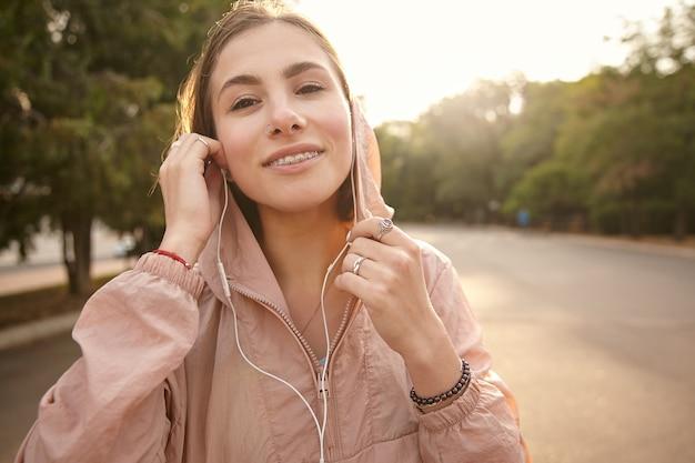 ヘッドフォンで音楽を聴いている、公園を歩いている、カメラを見て、嬉しいと感じている若い笑顔の女の子の写真。