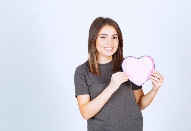 심장 모양의 선물 상자를 들고 젊은 웃는 여자의 사진.