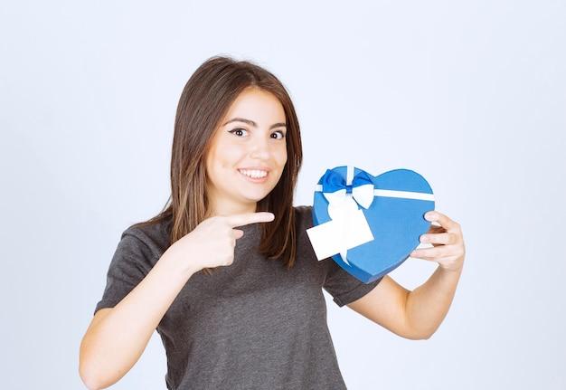 심장 모양의 선물 상자를 가리키는 젊은 웃는 여자의 사진.
