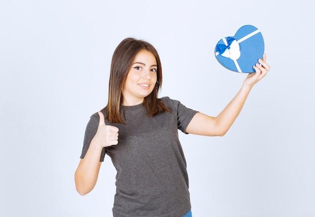 Фото молодой улыбающейся женщины, показывающей большой палец вверх и держащей подарочную коробку в форме сердца.