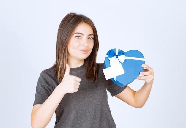 엄지 손가락을 표시 하 고 심장 모양의 선물 상자를 들고 젊은 웃는 여자의 사진.
