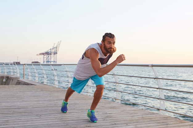 해변과 아침 스포츠에서 젊은 스포티 한 수염 실행 남자의 사진.