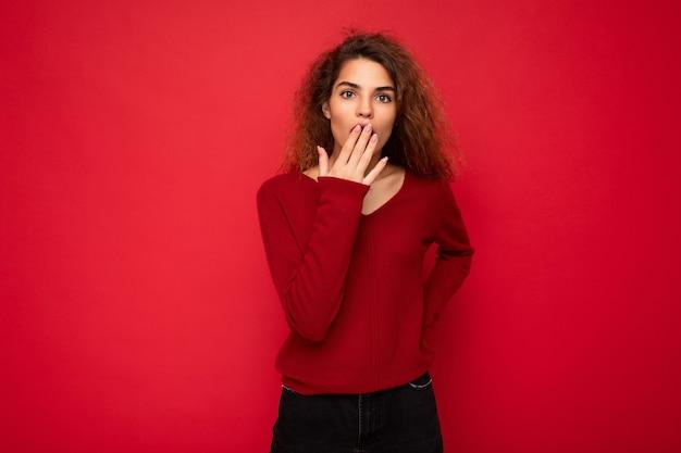 Фотография молодой удивленной, удивленной привлекательной брюнетки вьющейся женщины с искренними эмоциями носит
