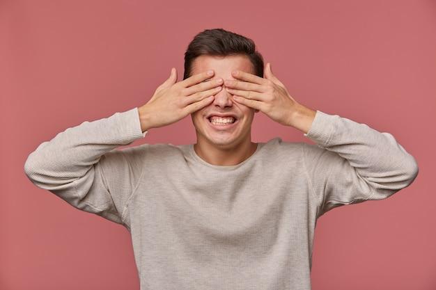 Фотография молодого удивленного парня в пустом длинном рукаве закрывает глаза ладонями, стоит на розовом фоне с широко открытыми глазами и кричит.