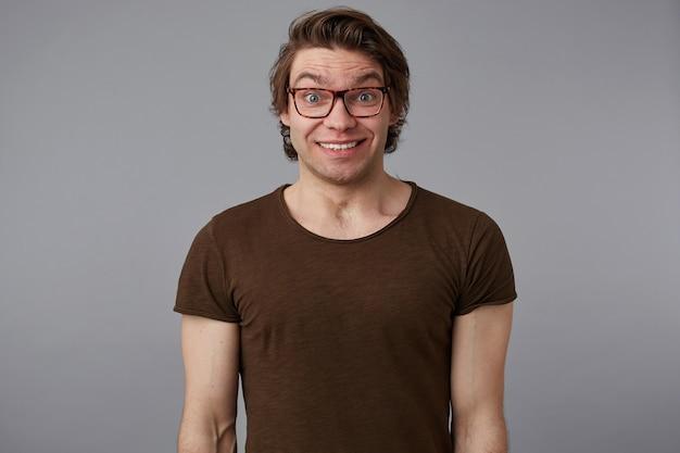 안경을 쓴 젊은 놀란 잘 생긴 남자의 사진은 기본 티셔츠를 입고 회색 배경 위에 서서 크게 미소 짓고 행복하고 궁금해 보입니다.