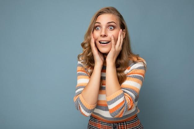 カジュアルなストライプを身に着けている誠実な感情を持つ若い驚いたかなり素敵な金髪の巻き毛の女性の写真