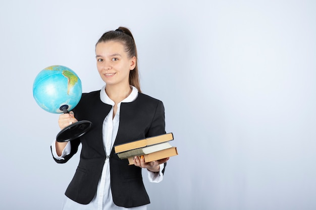 白で本と地球を保持している若い先生の写真。