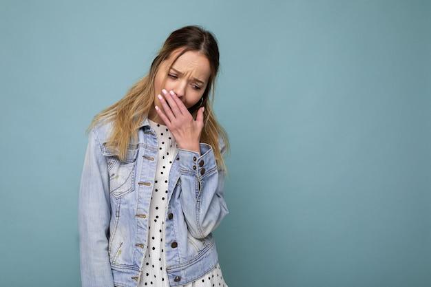 Фото молодой усталой усталой красивой блондинки с искренними эмоциями в джинсовой синей куртке