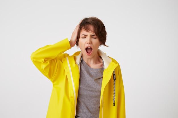 Фотография молодой несчастной короткошерстной дамы в желтом плаще от дождя, держащей голову, ощущающей сильную мигрень, хмурящейся и кричащей, стоит на белом фоне.