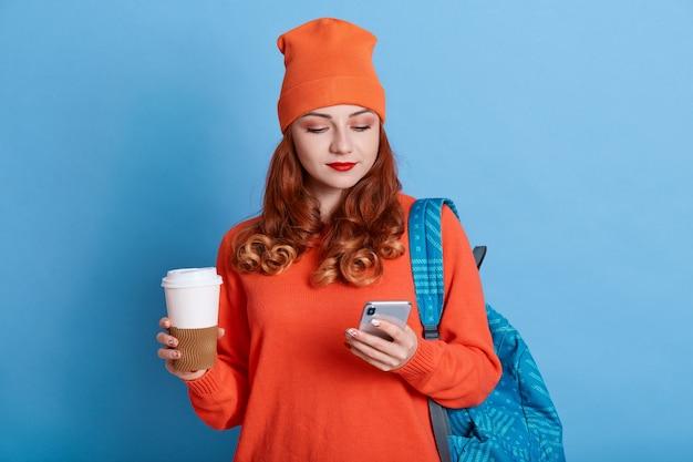 На фото молодая женщина чувствует себя хорошо после полученного письма, держит кофе с собой, имеет рюкзак