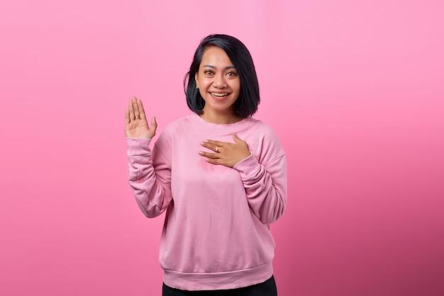 胸に若い女性の幸せなポジティブな笑顔の手の写真は、ピンク色の背景に分離された真実を誓う約束をします