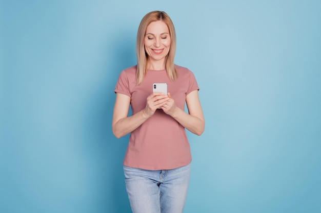 若い女性の幸せなポジティブな笑顔の写真は、青い色の背景の上に分離された携帯電話チャットタイプのsmsをオンラインで使用します
