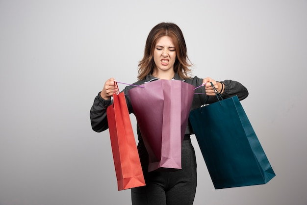 ショッピングバッグを持っている若い女性の写真。