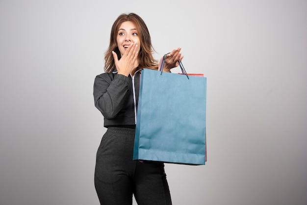 Фото молодой женщины, держащей хозяйственные сумки.