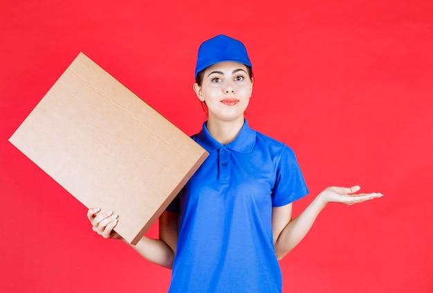 赤い壁に段ボール箱を保持している青い服を着た若い女性の写真。