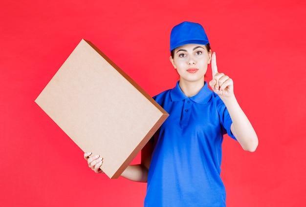 Фотография молодой женщины в синем обмундировании, держащей картонную коробку над красной стеной.
