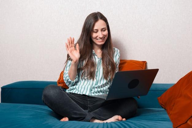 ソファに座ってラップトップでオンライン会議を持っているカジュアルな若い女性の写真