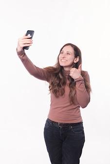 캐주얼 셀카를 복용하고 엄지 손가락을 보여주는 젊은 여자의 사진