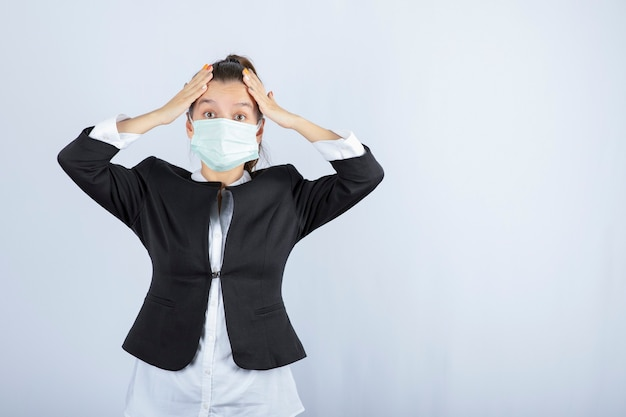 Фото молодой женщины в маске, держа ее голову на белом фоне. фото высокого качества