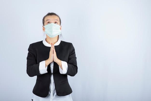 Фото молодой женщины в маске, молящейся на белой предпосылке. фото высокого качества