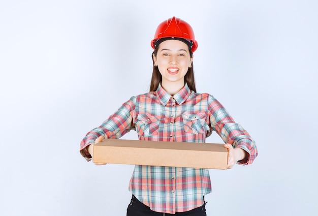 カートンボックスを保持している赤いヘルメットの若い女性の写真。