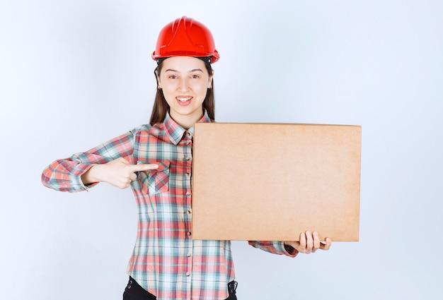 カートンボックスを示す赤いヘルメットの若い女性の写真。