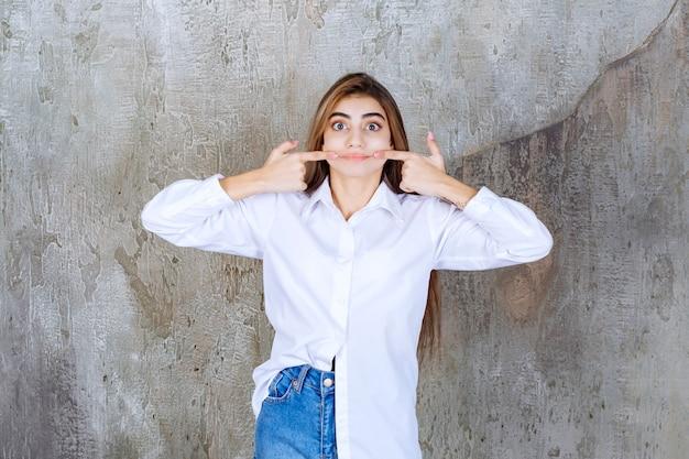 大理石の上に立っている白いブラウスの若い女性の写真