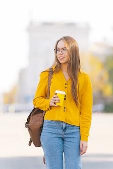 街の通りを歩いて持ち帰りコーヒーを保持している黄色の若い女性の写真