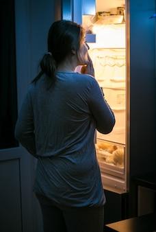 深夜に冷蔵庫の中を見ている若い女性の写真