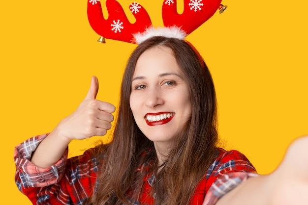 Фотография молодой женщины, делающей селфи с телефоном и показывая большой палец вверх, готовая к зимним праздникам