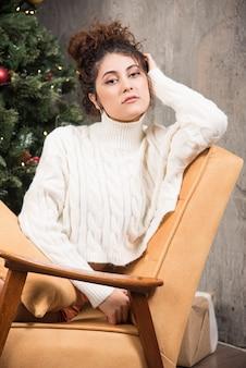 クリスマスツリーの近くの快適な椅子に座っている若い女性の写真