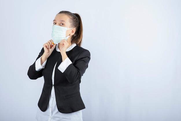 白い背景の上の医療マスクを身に着けている若い女性の写真。高品質の写真