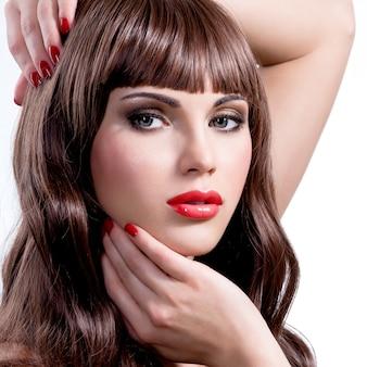 美しさの長い巻き毛と明るいメイクの若い女性の写真。スタジオでポーズをとるファッションモデル。