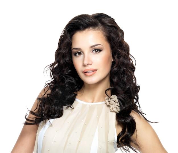 長い巻き毛の美しさを持つ若い女性の写真。スタジオでポーズをとるファッションモデル。