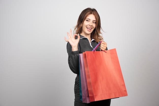 Фото молодой женщины с хозяйственными сумками и махнув рукой.
