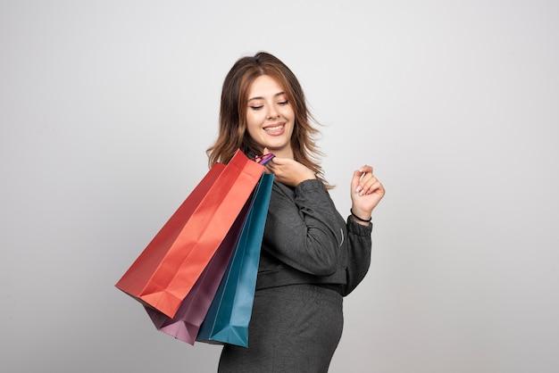 ショッピングバッグと手を振っている若い女性の写真。