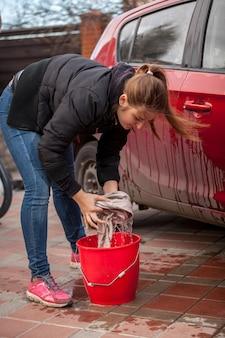 Фотография молодой женщины, выжимающей тряпку во время мытья автомобиля на открытом воздухе