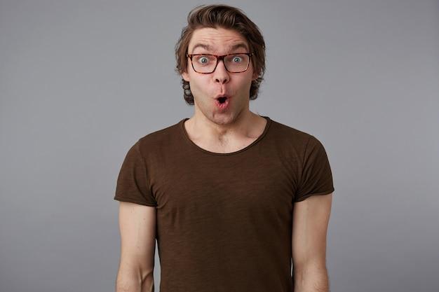 안경을 쓴 젊은 궁금해 잘 생긴 남자의 사진은 기본 티셔츠를 입고 회색 배경 위에 서서 크게 미소 짓고 행복하고 놀란다.