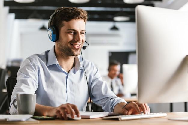 Фотография молодого работника 20-х лет в офисной одежде и наушниках, улыбающегося и говорящего с клиентами в колл-центре