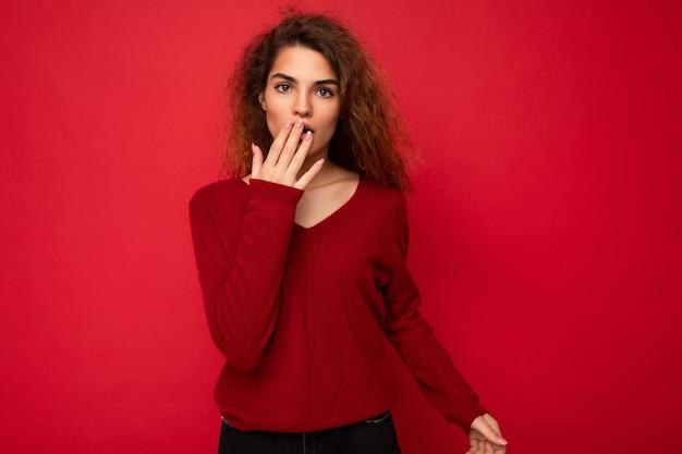 Фотография шокированной изумленной привлекательной кудрявой брюнетки с искренними эмоциями в повседневной одежде