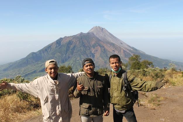 Фотография молодежи, которая шутит с друзьями на горе