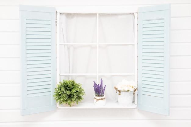 写真花と古い青いシャッター窓、白い家
