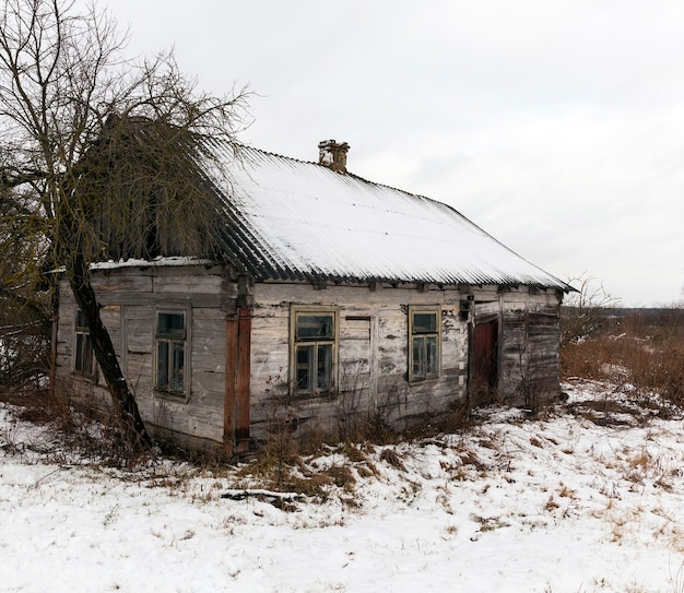 Photo of the old collapsing one house, covered with snow after snowfall