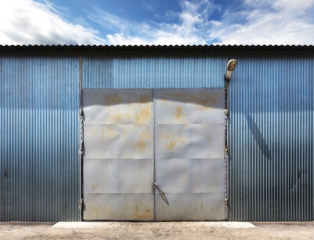 Photo of old grunge closed warehouse, blue sky on background.