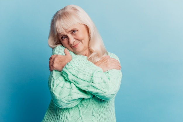 Photo of old lady embracing herself isolated on blue background