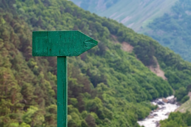 Photo of an old road sign against a blurred mountain landscape